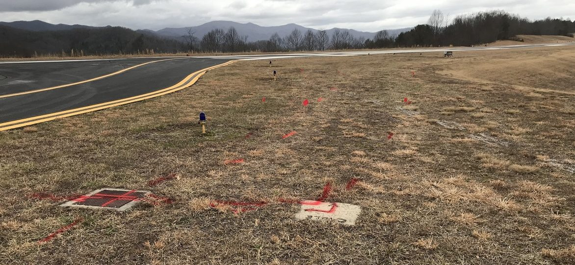Red marks on ground depict electrical lines for runway lighting.