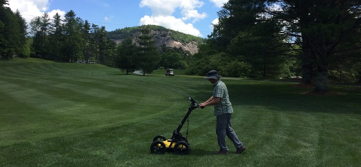 Technician using GPR at golf coarse in Cashiers, NC - rock cliff in background