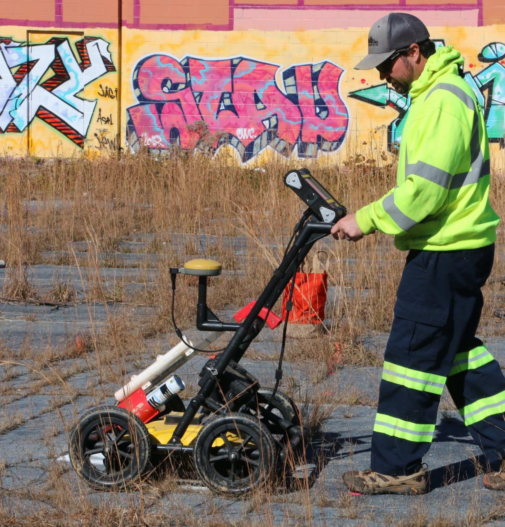 Technician using GPR for borehole clearance at abandoned industrial site - graffiti in background