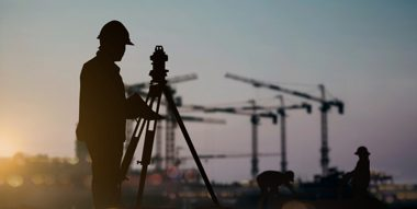silhouette of surveyor with cranes in background