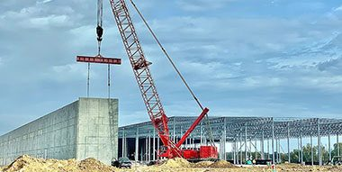 Red crane with industrial construction site in background.